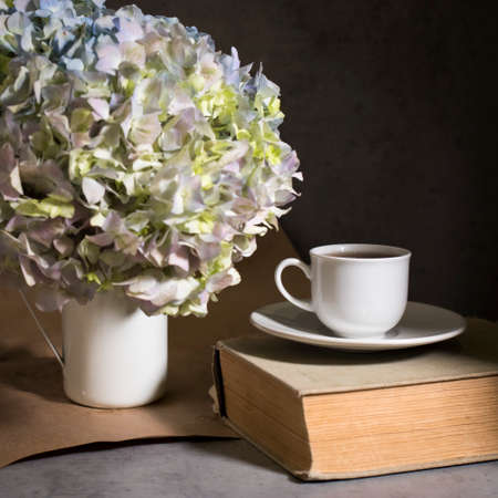 A branch of green pastel hydrangeain an enameled mug instead of a vase with white cup of coffee and vintage book on a on a gray craft vintage background. Copy space