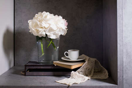 White hydrangea in a glass vase with a small cup of coffee on a book with a notebook. on a gray craft background. Imagens