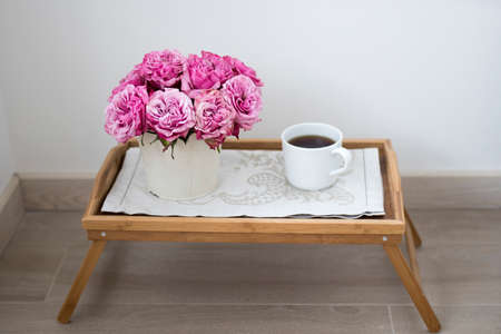 Bouquet of pink roses in a white tin bucket with the white cup of coffee on a wooden tray. Copy space