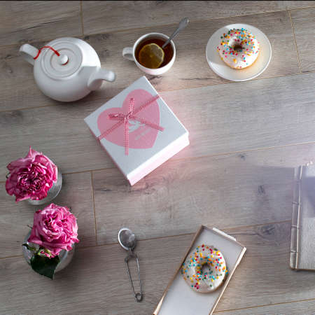 Tea ceremony. A white teapot, a cup of tea with lemon, a notebook, a cardboard box with a gift with the inscription Best wishes, donuts and two round vases with terry roses.