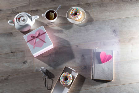 Tea ceremony. A white teapot, a cup of tea with lemon, a notebook, a cardboard box with a gift with the inscription Best wishes, donuts on the grey table. Copy space