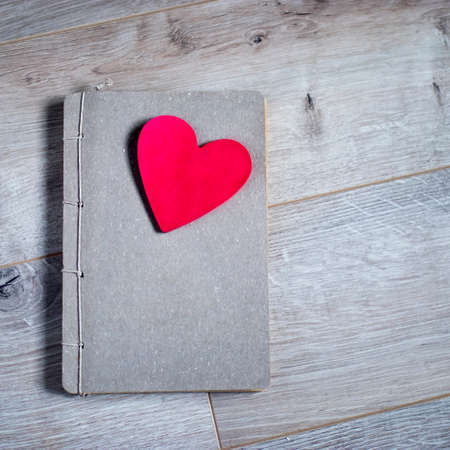 Kraft notebook with red paper heart on a gray wooden table surface. The texture of birch. Copy space Фото со стока