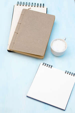 An open notebook on springs with white craft paper lies on a table. Concept for business ideas. Home office workplace. Flat lay, Business-finance or education concept with copy space.