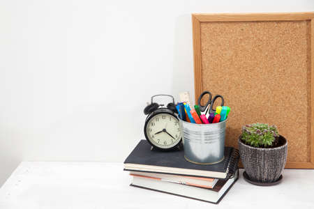 Copy space. Workplace office worker. Alarm clock, succulent in ceramic pot, writing board, bucket with scissors, felt-tip pens, ruler, three notebooks on student's desk.
