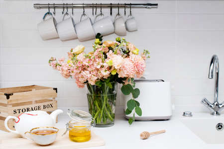 wedding bouquet of pink and orange lisianthus, antirrhinum and eucalyptus in glass vase on kitchen table. Black tea in a white cup, honey jar and spoon for honey, lemon closeup on a white kitchen