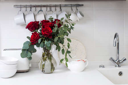 wedding bouquet of red rose and eucalyptus in glass vase on kitchen table. Black tea in a white cup, honey jar and spoon for honey, lemon closeup on a white kitchen. Decoration of kitchen
