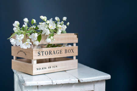 Wooden box for storing things with the inscription Sweet home with an apple flowering branch on a white vintage stool against a dark blue wall. Copy space