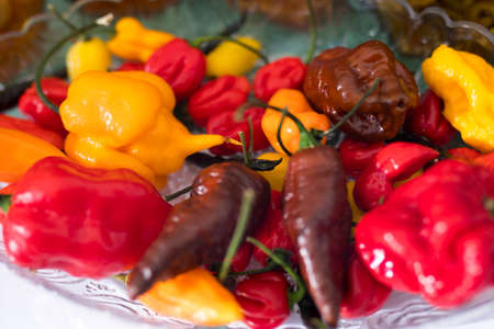 Various types of hot yellow, red, brown peppers in a bowl for table decoration. Market