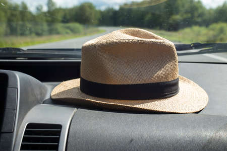 A straw hat lies in front of the front windshield in a car while traveling.
