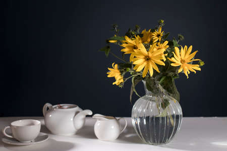 A bouquet of yellow jerusalem artichoke in a transparent vase on against black background on the table. White teapot, cup and saucer and milk jug for tea drinking.
