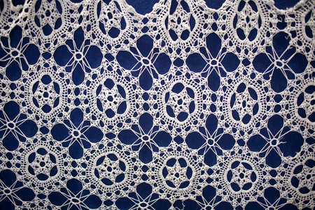Crocheted openwork napkin on a blue background.