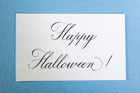 Calligraphic inscription Happy halloween on white textured paper, on blue paper card. Decoration