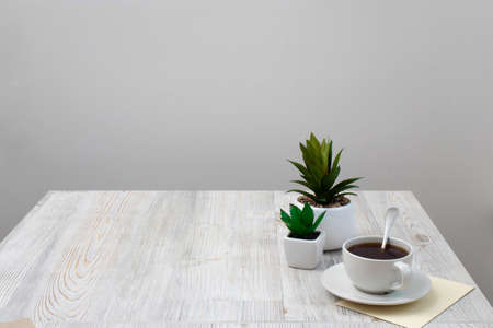 Office desk wood table of Business work place, artificial plants and coffee cup with copy space on grey wooden table. Banco de Imagens