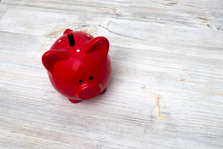 Red piggy bank on wooden grey table background. Finance Savings and money wealth concept. Zdjęcie Seryjne