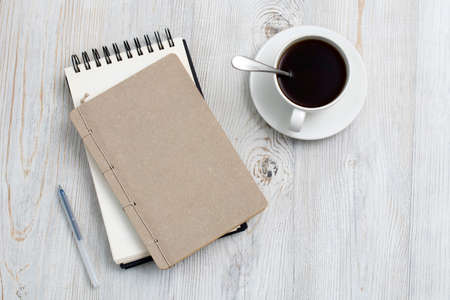 desk office with blank notepad, coffee cup and pen on wood table. Flat lay top view copy space. Top view