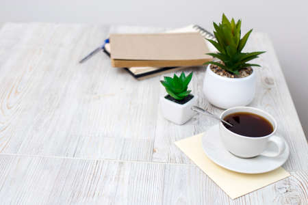 desk office with blank notepad, coffee cup and pen on wood table. Flat lay top view copy space.