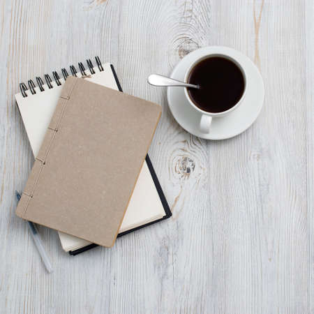 desk office with blank notepad, coffee cup and pen on wood table. Flat lay top view copy space. Top view Imagens