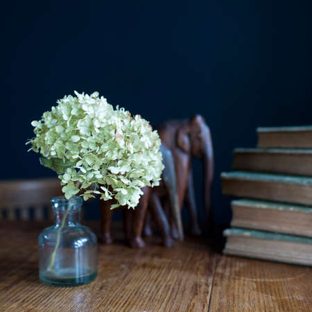 A dried hydrangea flower in a glass transparent vase on a wooden table near a dark blue wall. Stack of old bound books. Copy space. Selective focus