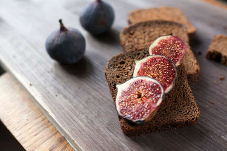 Bunch of fresh ripe figs on wodden brown background. Tropical fruit Banco de Imagens