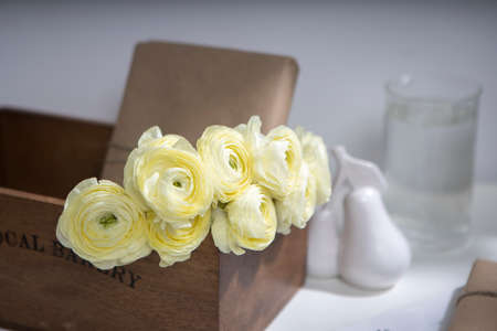 Bouquet of yellow ranunculus in a wooden box with wrapped gifts on a pale gray background