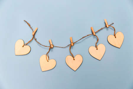 Wooden hearts pinned to a rope with clothespins on a light blue background. Copy space