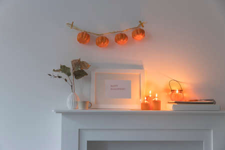 Preparing your home for Halloween. A garland of pumpkins on the wall above fake dresser panel. Frame with the inscription, orange candles and lantern. Corrugated vase with dried eucalyptus branch. Фото со стока