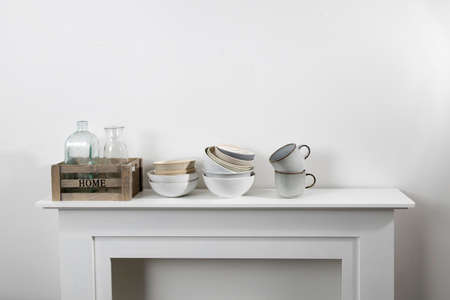 kitchen utensils, cups of different sizes and shades, bowls, bottles, storage items, are on a white dresser.