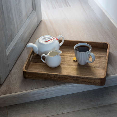 A wooden tray with a cup of tea, a teapot, a milk jug is on the floor in the doorway. Фото со стока