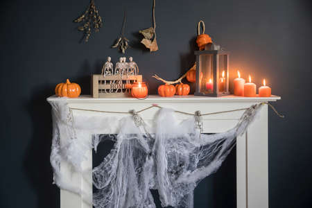 Halloween home decoration. Plastic toy skeletons in a wooden box on a fireplace against a dark blue wall. A garland of skeletons. Cobweb on the dresser. Orange candles and lantern. Фото со стока