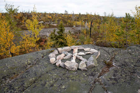 Swamp or lake with megalithic seid boulder stones, dead trees in nature reserve on mountain Vottovaara, Karelia, Russia. Shamanic circle made of stones on a high mountain