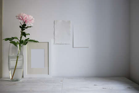 Scandinavian style. Interior Design. Large pink chrysanthemum in a long glass vase. Photo frame. Two blank sheets of paper on the wall. Empty space for text