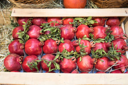 Fresh harvest, pomegranates in a box are sold in the market