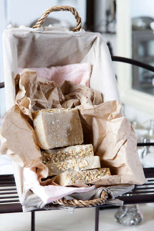 Handmade oatmeal soap in a wicker basket with beige bedding for sale, decoration and fragrances