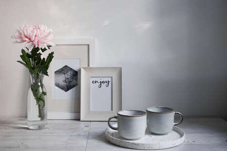 Scandinavian style. Interior Design. Large pink chrysanthemum in a long glass vase. Two cups of different size. Frame for photo. Empty space for text