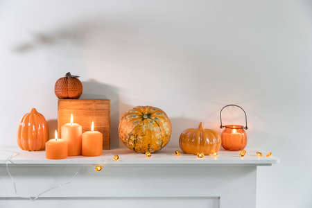 Porcelain and natural pumpkins, orange candles on a white table, Halloween decorations.