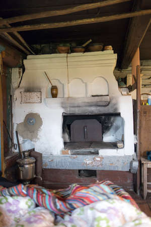 Russian stove. Interior of old russian home with traditional oven Фото со стока