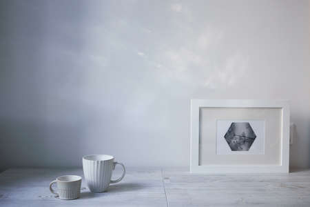 Scandinavian style. Interior Design. A white cup of different size, a frame for a photo are on the table. Empty space for text Фото со стока
