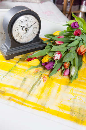 A bouquet of multicolored tulips lies on the table next to the old table clock