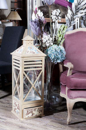 Artificial flowers of hydrangea and dried flowers next to a large handmade lantern. Purple armchair in the interior