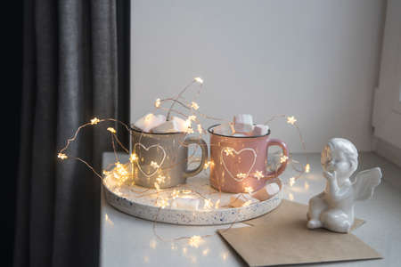 Apartment decoration for Christmas. Gray and pink mugs with painted white hearts with cocoa, marshmallows on tray on the window, composition decorates the interior on the eve of Christmas. Copy space Фото со стока