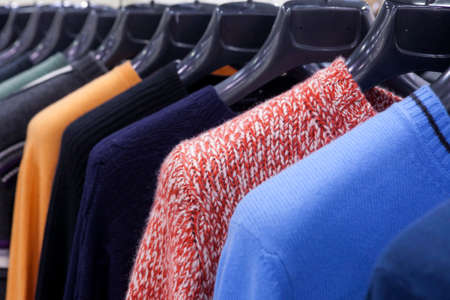 Women's multicolored knitted and crocheted sweaters, jackets hang on hangers in the store Фото со стока