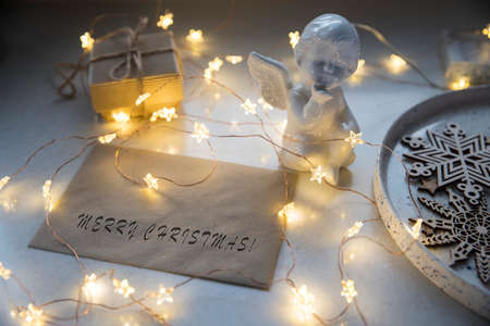 Apartment decoration for Christmas. A plaster figure of an angel is on a beige envelope with congratulations. An asterisk garland shines all over the frame. Copy space
