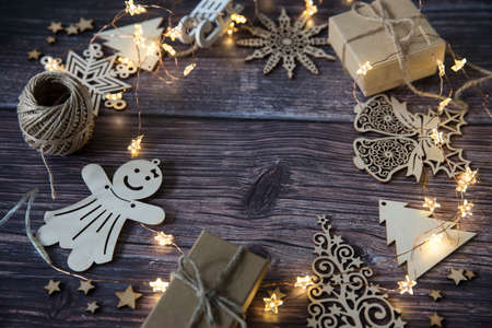 Glowing garland star, two gray boxes with gifts tied with twine, plywood Christmas decorations carved from wood on a wooden table surface. Copy space Фото со стока