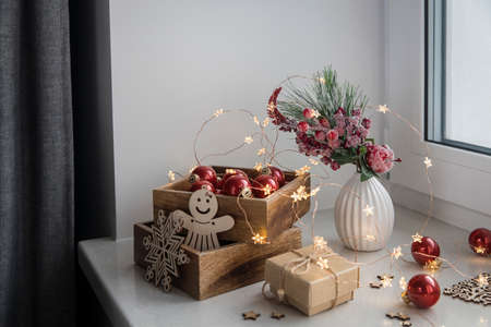 An artificial spruce branch, decorated with ivy leaves, apples and hawthorn berries. Lighted candles in wooden box, red glass balls, winter composition decorates interior on eve of Christmas