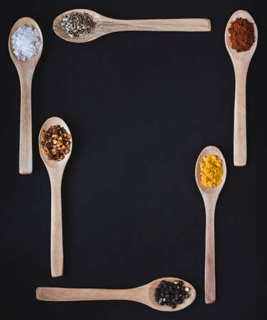 Spices arranged on wooden spoons in a square type border Stock Photo