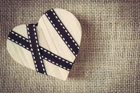 Wooden heart blank with decorated ribbon on sack material background Stock Photo