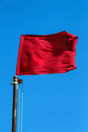 Red flag flying on rusted pole