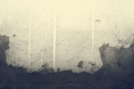 Photo of a grungy wall with plaster at the bottom