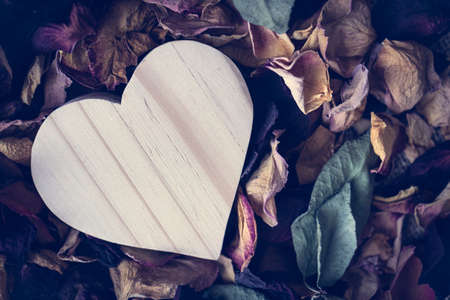 Blank wooden heart shape on bed of dried rose petals