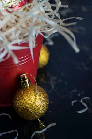 Gold Christmas balls resting against a red bucket. Stock Photo